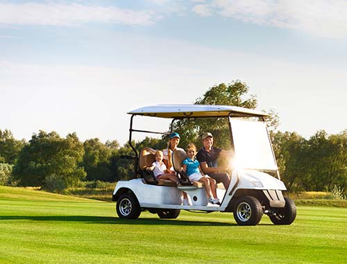 A family takes a ride in a golf cart