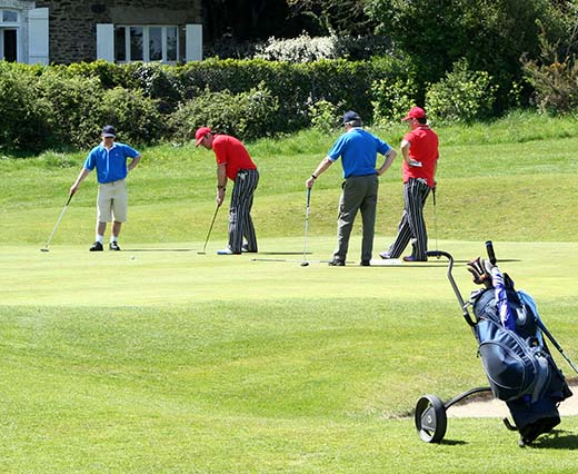 A group of men putt at a hole